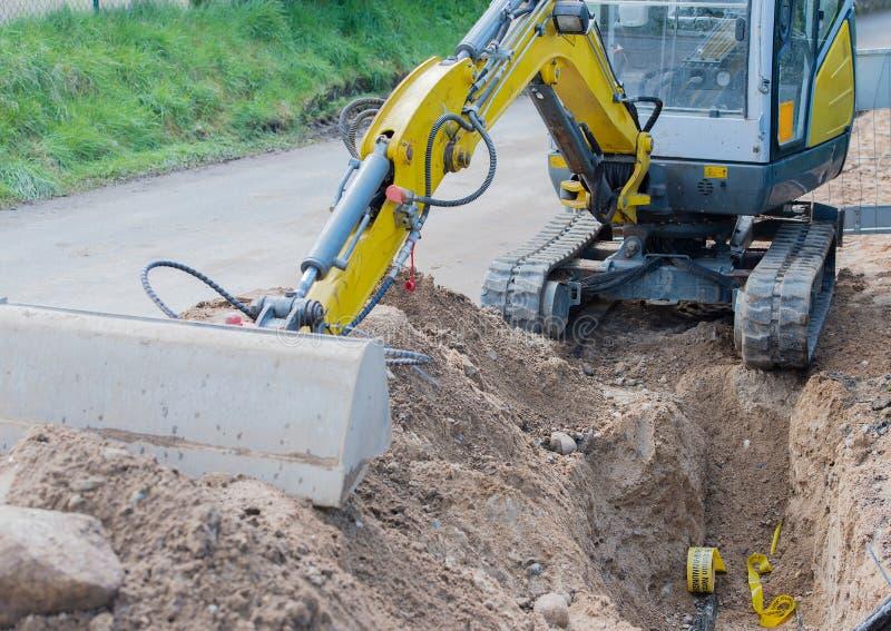 Мини экскаватор для дорожных работ для интернета и электропитания стоковое изображение rf