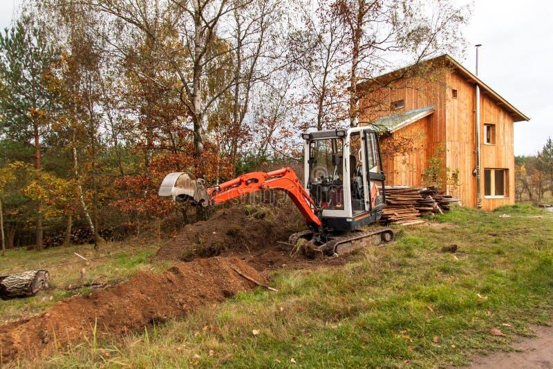 Мини экскаватор на строительной площадке Конструкция дома семьи около леса стоковое изображение