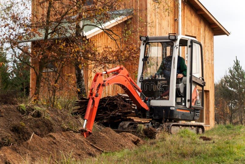 Мини экскаватор на строительной площадке Конструкция дома семьи около леса стоковая фотография rf