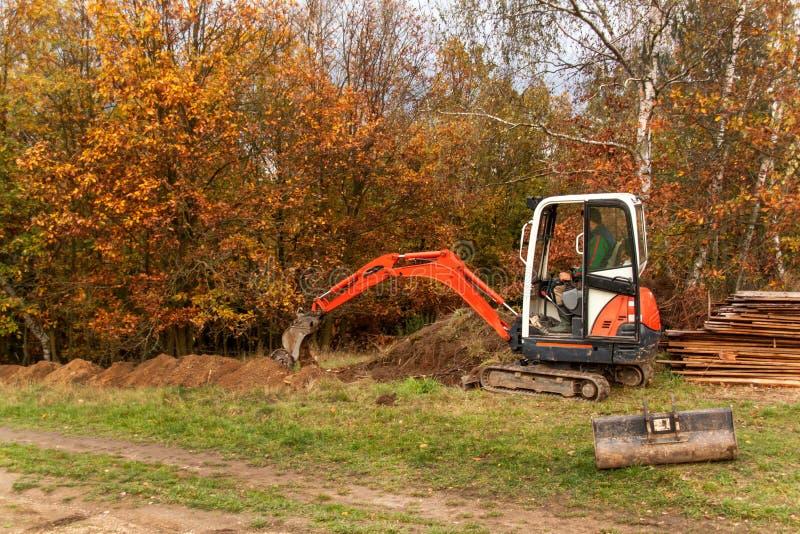 Мини экскаватор на строительной площадке Конструкция дома семьи около леса стоковые фото