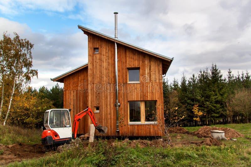 Мини экскаватор на строительной площадке Экскаватор регулирует местность вокруг дома стоковая фотография