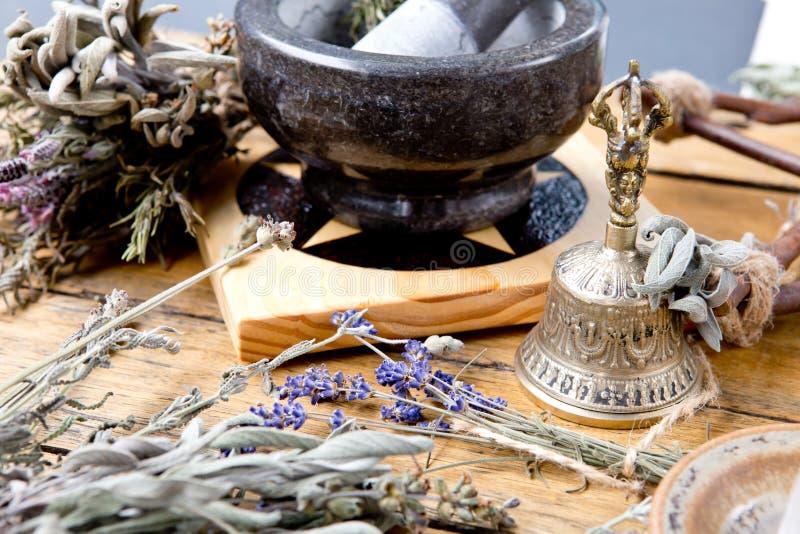 Миномет и пестик на плитке с высушенными пачками травы, латунном колоколе алтара pentacle, кристалле кварца на деревянной предпос стоковые изображения rf