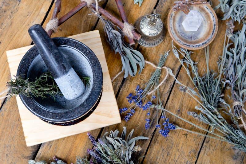 Миномет и пестик с высушенными травами, латунным колоколом, кристаллом кварца и пентаграммой ветви на деревянной предпосылке стоковая фотография rf