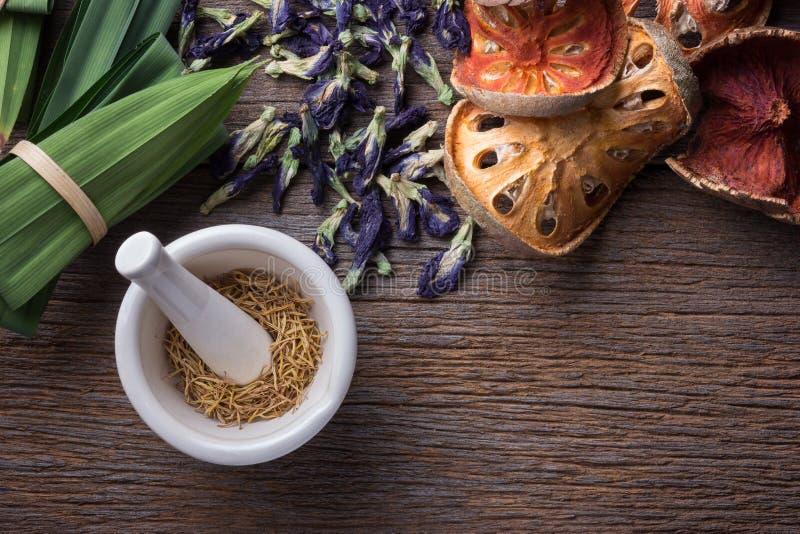 Миномет и пестик с травой на таблице древесины grunge стоковое изображение