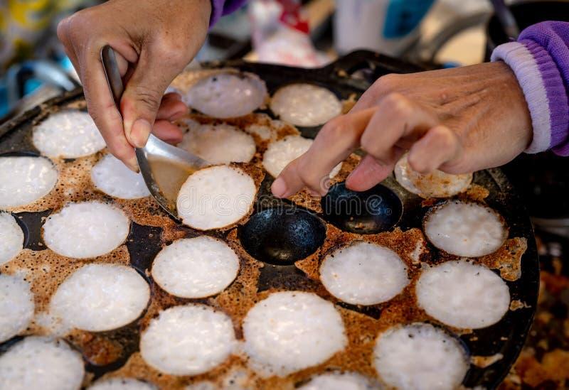 """Миномет-провозглашанное тост печенье или """"Kanom Krok """"тайский традиционный десерт Рука женщины извлекая Kanom Krok из плиты ложко стоковое фото rf"""