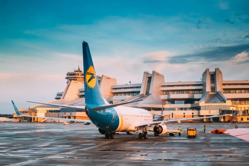 Минск, Беларусь Воздушные судн плоский Боинг 737 стойки авиакомпаний международных перевозок Украины на авиапорте Минска национал стоковая фотография