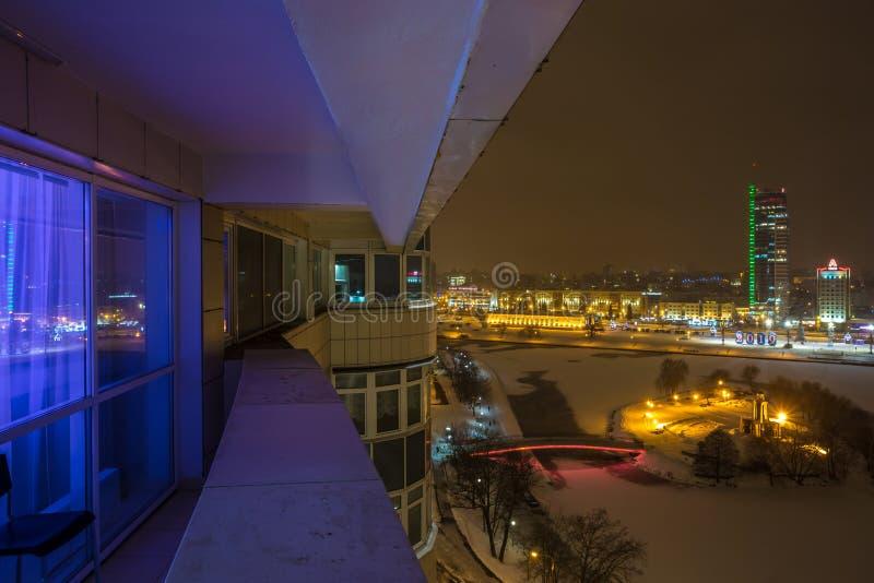 МИНСК, БЕЛАРУСЬ - ДЕКАБРЬ 2018: света города ночи Светлый небоскреб отраженный в воде озера стоковое изображение rf