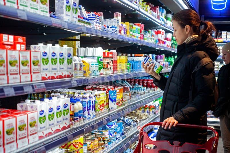 Минск, Беларусь, 25-ое марта 2018: Молоко человека ходя по магазинам в гастрономе Ингредиенты, объявление или срок годности чтени стоковые изображения rf