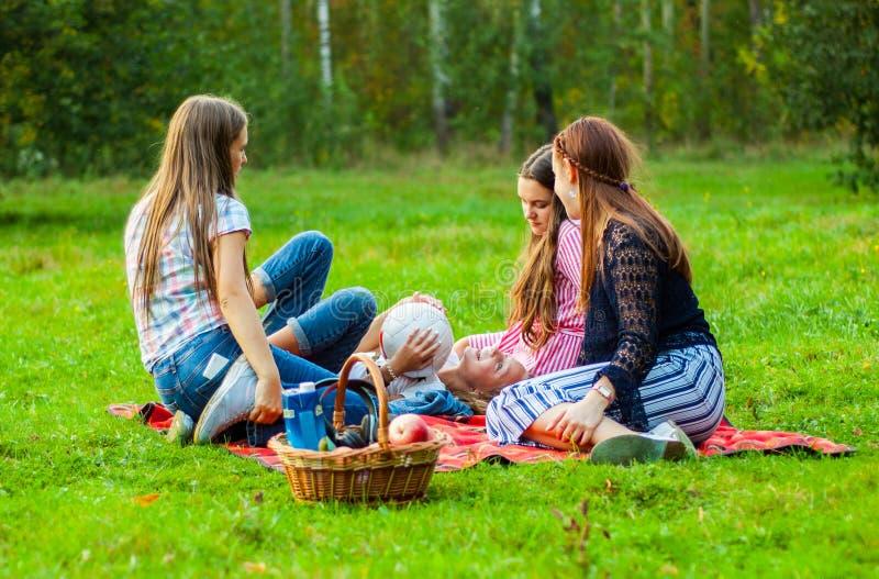 Минск, Беларусь - 21-ое сентября 2018: Группа в составе друзей молодые девушки подростка имея потеху совместно на траве стоковое изображение rf