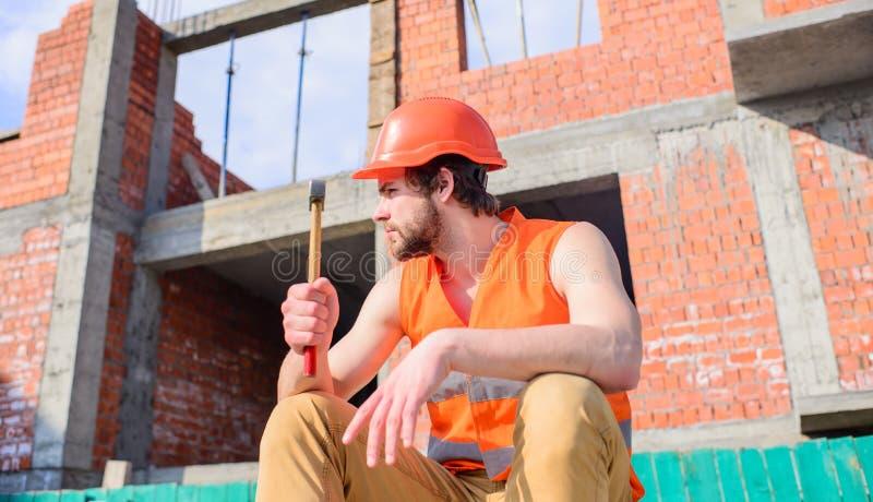 Минута взятия, который нужно ослабить Рабочий день пролома взятия молотка человека на строительной площадке Жилет построителя и с стоковая фотография rf