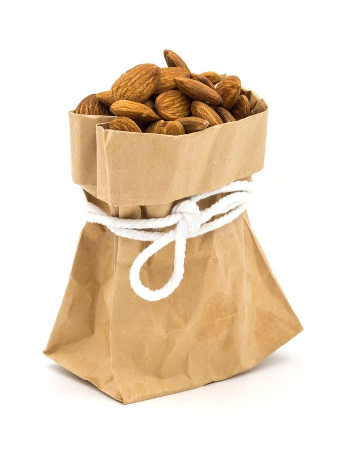 Миндалина в коричневой сумке на белой предпосылке стоковое фото