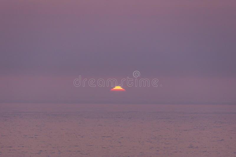 Мираж захода солнца - солнце странной формы немногой момент перед идти под горизонтом стоковая фотография rf