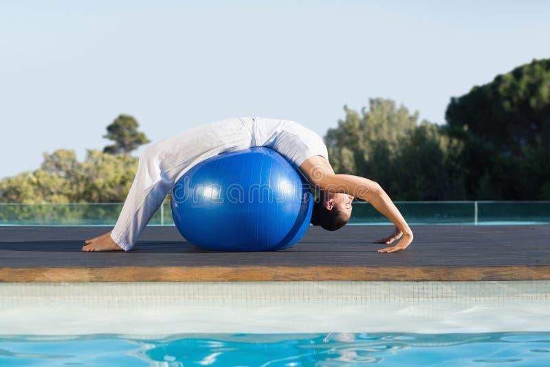 Мирное брюнет в представлении кобры над poolside шарика тренировки стоковые фото