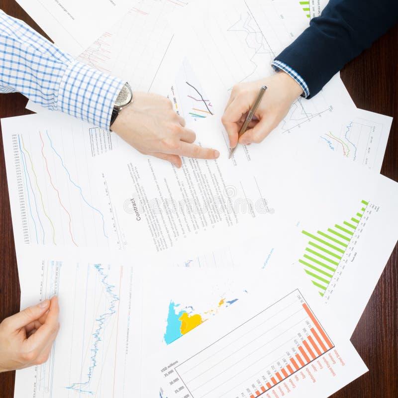 Мир дела и свои символы - 2 бизнесмена работая на некоторых финансовых данных на столе стоковые фото