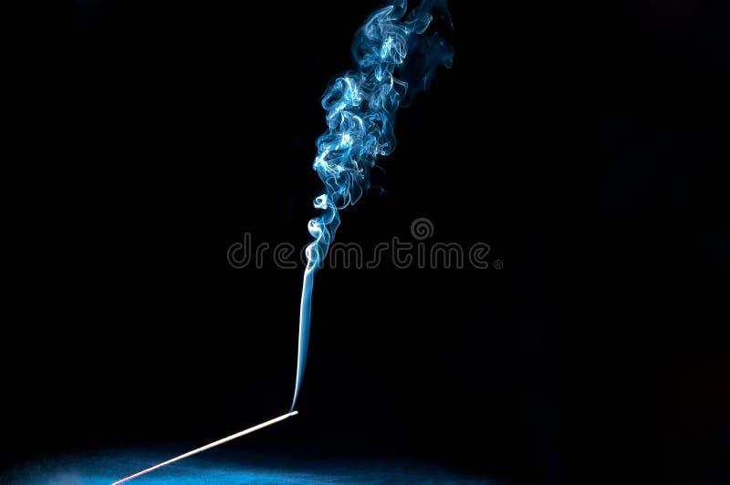 Мистическая горящая ручка ладана с надушенным дымом используемым для раздумья, mindfulness, духовности и релаксации стоковые фото