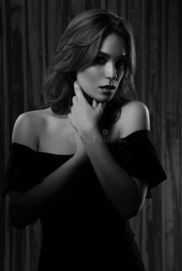 Мистическая сексуальная женщина макияжа держа руки шея с длинным курчавым стилем причесок и смотря страсть на предпосылке темной  стоковое изображение