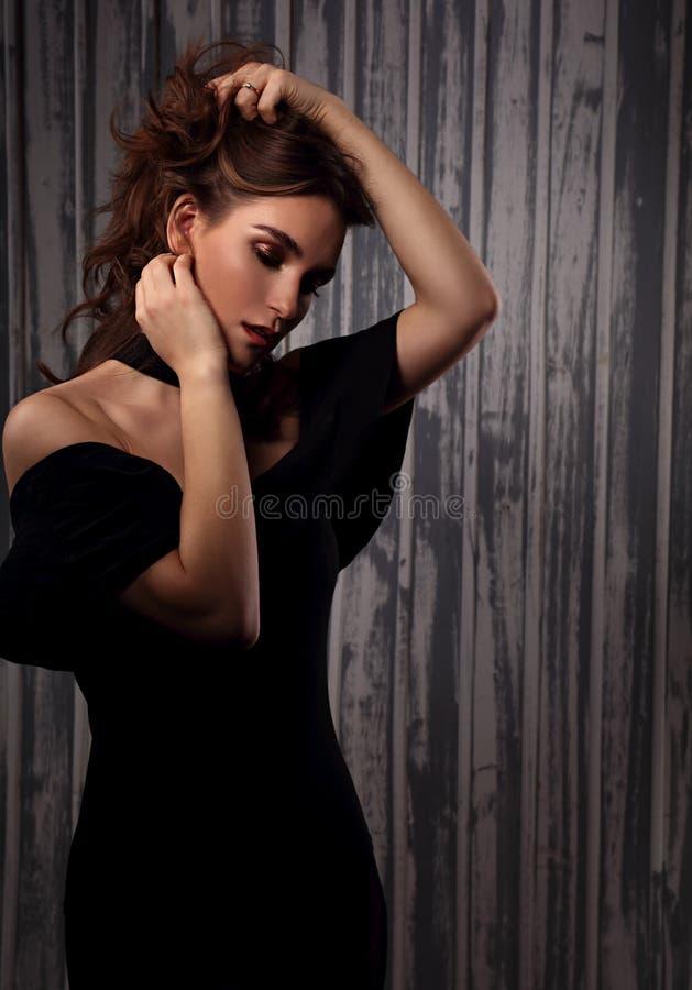 Мистическая сексуальная женщина макияжа держа стиль причесок руки длинный курчавый и смотря страсть на предпосылке темной тени ис стоковые фотографии rf