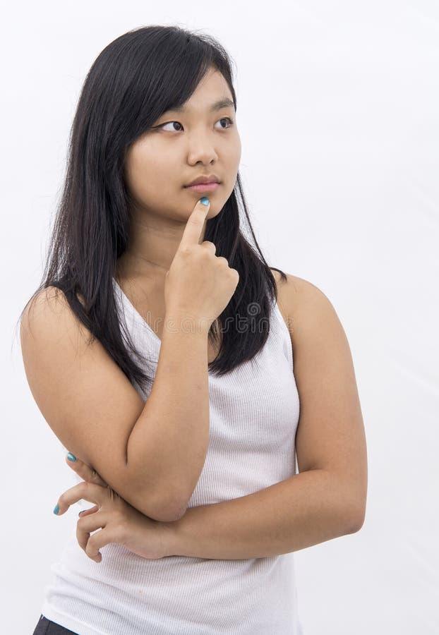 Милая азиатская девушка на изолированный думать предпосылки стоковое фото