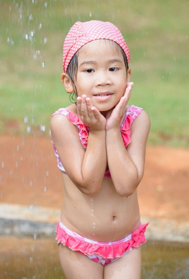 Милая азиатская девушка принимая ливень стоковые фото