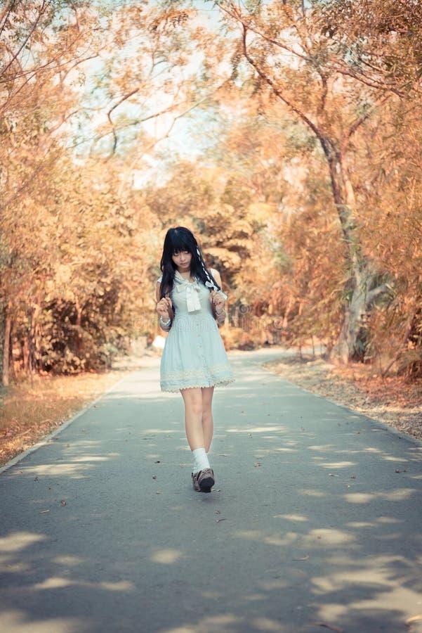 Милая азиатская тайская девушка идет на путь леса самостоятельно в нежности стоковое изображение