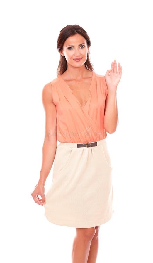 Милая дама брюнет в элегантной юбке приветствуя вас стоковое фото