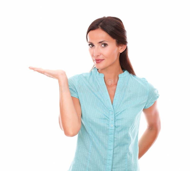 Милая дама в голубой рубашке держа правую ладонь вверх стоковые фото