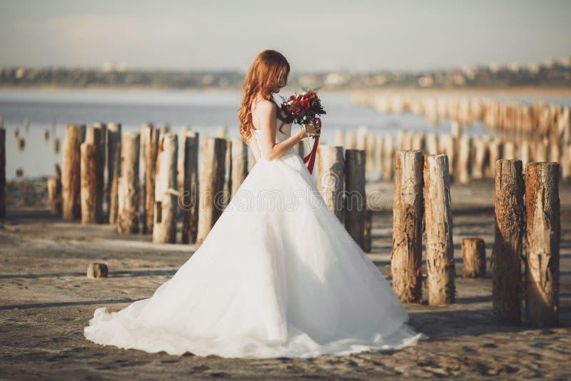 Милая дама, невеста представляя в платье свадьбы около моря на заходе солнца стоковые изображения