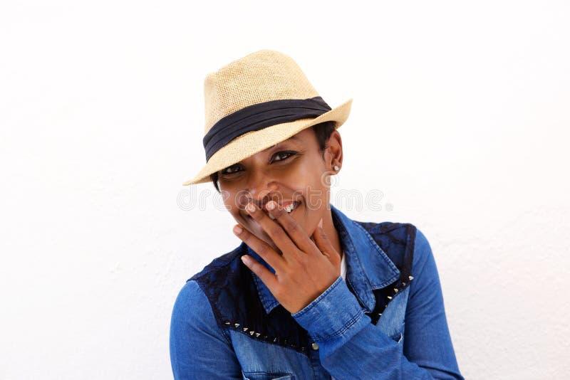 Милая Афро-американская женщина усмехаясь с ртом заволакивания руки стоковые изображения