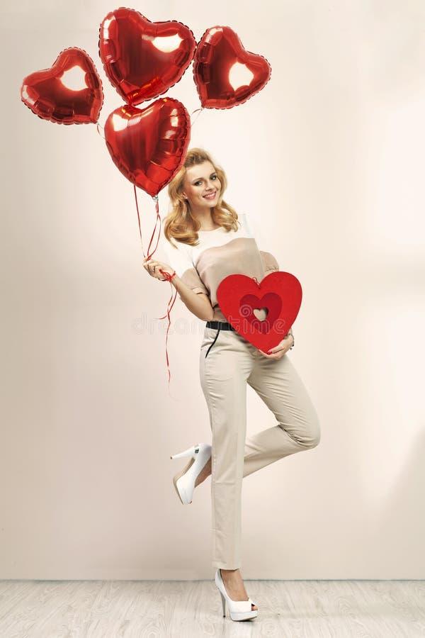 Милая белокурая девушка с пуком воздушных шаров стоковое изображение rf