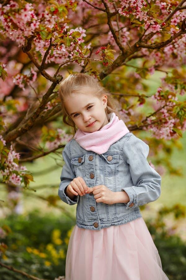 Милая белокурая девушка усмехается против предпосылки розового бушеля Сакуры стоковое изображение