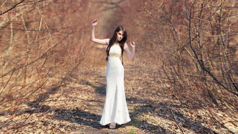 Милая девушка в белом платье в одичалом лесе стоковые изображения rf
