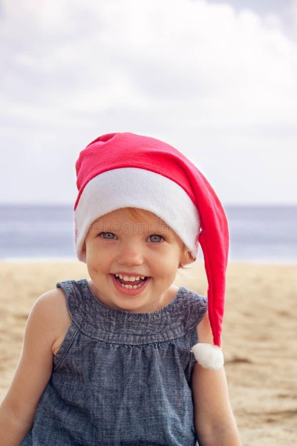 Милая девушка в шляпе Санты имея потеху на tropicals стоковые изображения