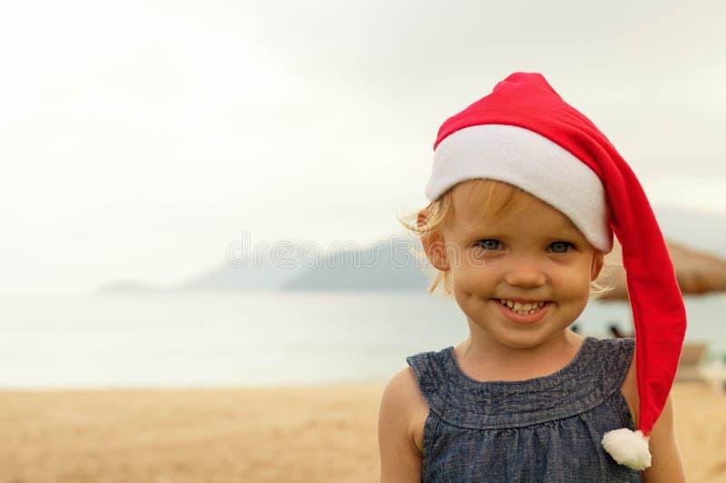 Милая девушка в шляпе Санты имея потеху на tropicals стоковое фото rf