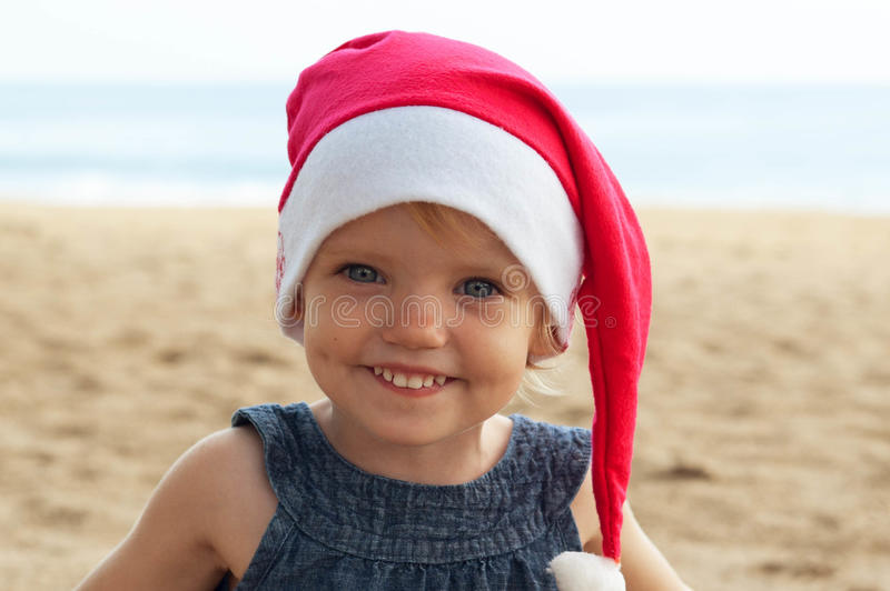 Милая девушка в шляпе Санты имея потеху на tropicals стоковая фотография