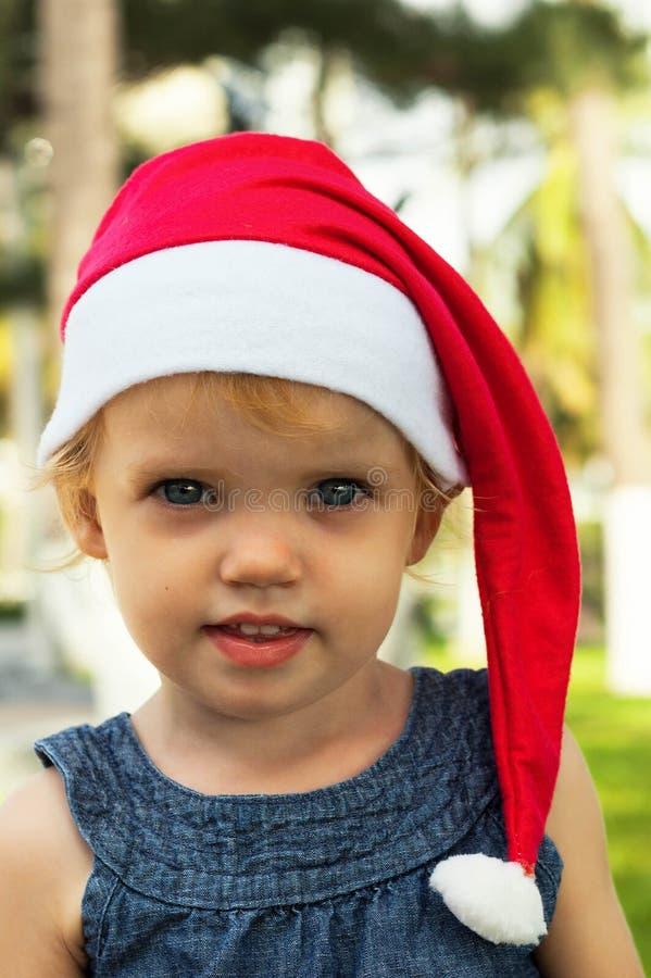 Милая девушка в шляпе Санты имея потеху на tropicals стоковое изображение rf