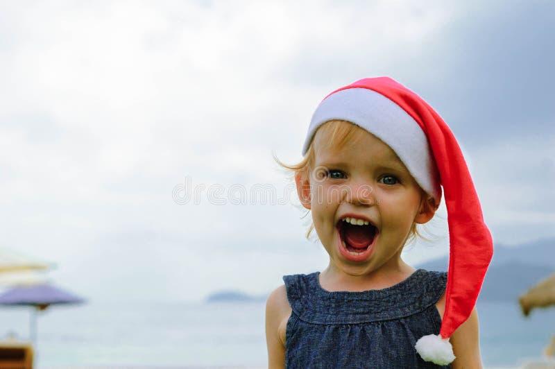 Милая девушка в шляпе Санты имея потеху на tropicals стоковые фотографии rf