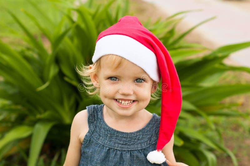 Милая девушка в шляпе Санты имея потеху на tropicals стоковое фото