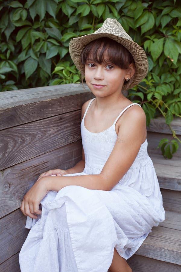 Милая девушка в шляпе сидя на крылечке стоковое фото rf