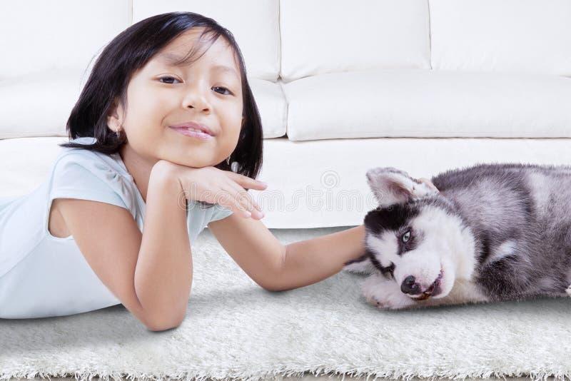 Милая девушка лежа с осиплым щенком дома стоковая фотография
