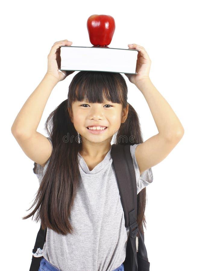Милая девушка держа книгу и яблоко на голове стоковая фотография rf