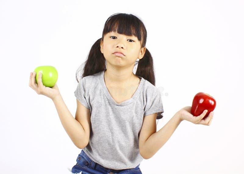 Милая девушка держа красное и зеленое яблоко стоковые изображения rf