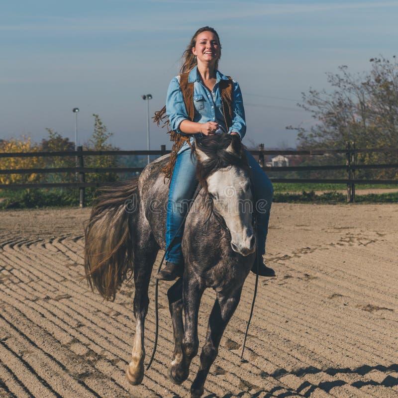 Милая девушка ехать ее серая лошадь стоковые изображения
