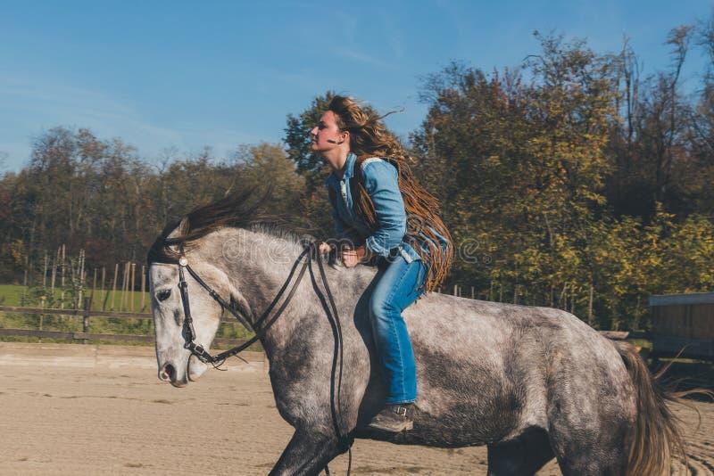 Милая девушка ехать ее серая лошадь стоковая фотография rf