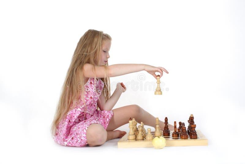 Милая девушка играя шахмат на белизне стоковые изображения rf