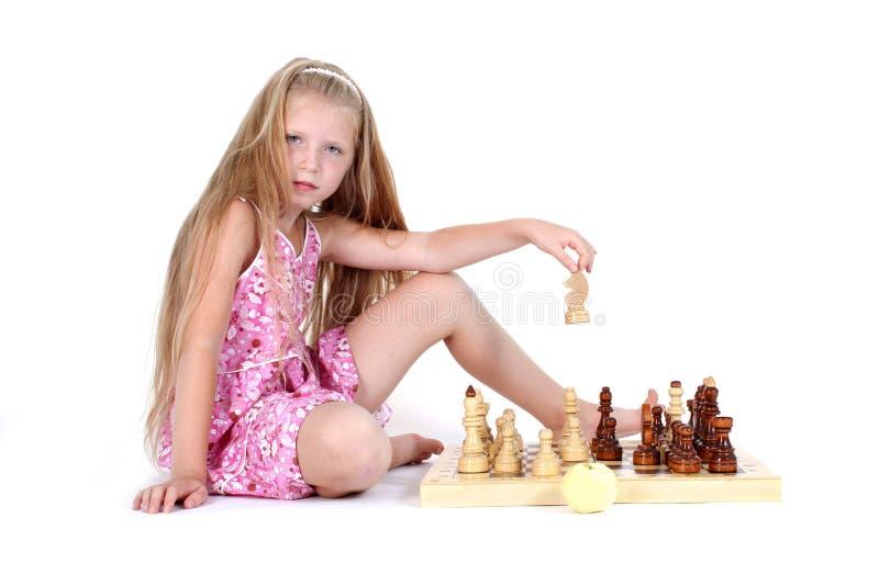 Милая девушка играя шахмат стоковые фотографии rf