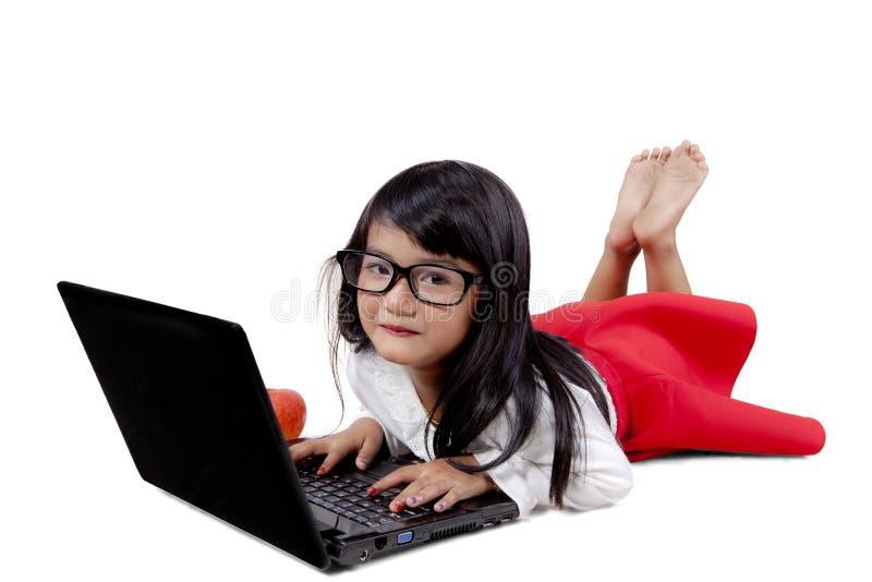 Милая девушка используя портативный компьютер на студии стоковая фотография