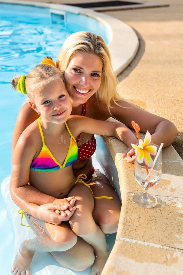 Милая девушка и красивая мать на бассейне стоковые изображения rf