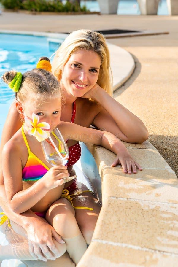 Милая девушка и красивая мать на бассейне стоковые изображения