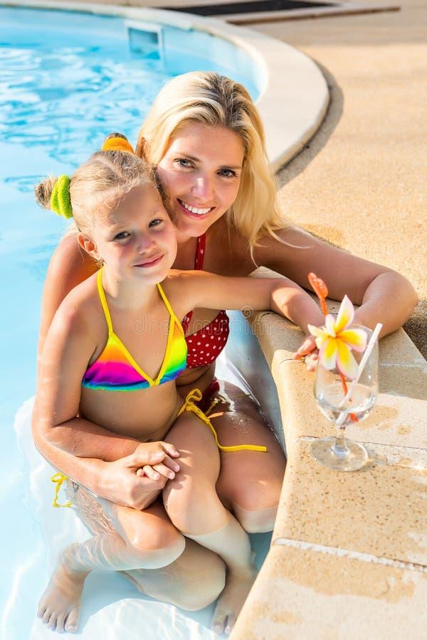 Милая девушка и красивая мать на бассейне стоковая фотография