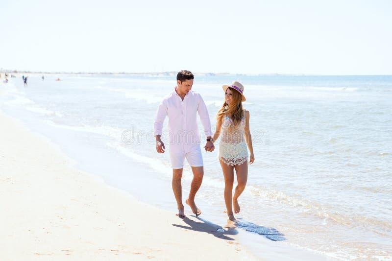 Милая девушка идя с ее парнем на пляже стоковые изображения
